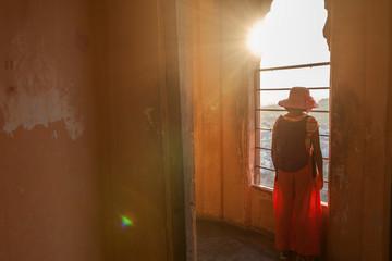 Teenage girl looking outside from a window