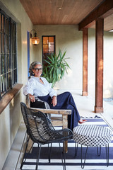 Portrait of beautiful and stylish mature woman interior designer with grey hair sitting on front porch