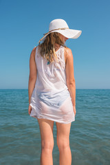 Young woman dressed in white standing on the sea shore