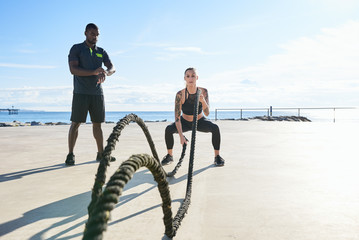 Sportswoman doing exercise with ropes with personal trainer.