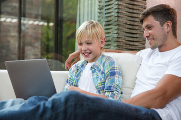 Father and son watching movie on a laptop