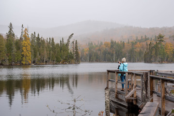 woman taking photo with smartphone of foggy autumn Canadian landscape