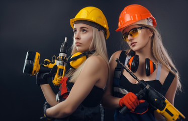 Fototapeta girl in construction clothes and protective equipment posing with a screwdriver obraz