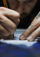 Close-up tattooist sketching