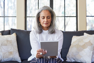 Mature woman with grey hair using a digital tablet in living room