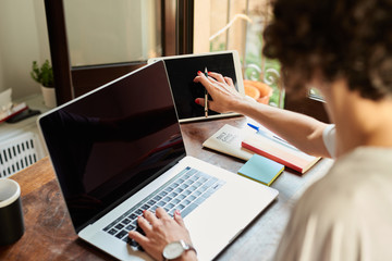 Woman working with tablet and laptop