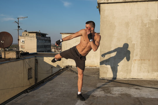 Kick Boxer Practising Moves On The Rooftop