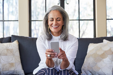 Mature woman with grey hair texting on cell phone in living room at home