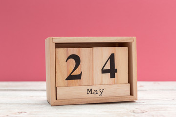 wooden cube shape calendar for may 24 on wooden tabletop