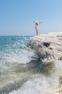 Woman with outstretched arms enjoying the seascape standing on a cliff