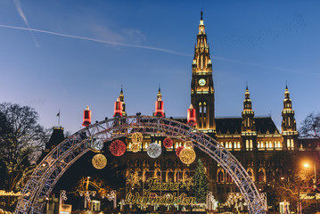 Vienna, Austria - December 24, 2017. Traditional Christmas market in front of the Rathaus City hall of Vienna. Xmas fair decorated with lights and Viennese town-hall on the Rathausplatz square.
