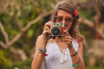 Giirl posing with retro vintage camera outdoors.