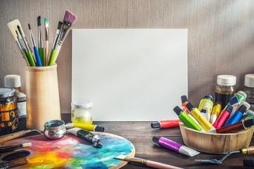 Painter equipment in a artist studio: empty canvas, tube of oil paint, art brushes, palette knife lying.  Artist workshop background.