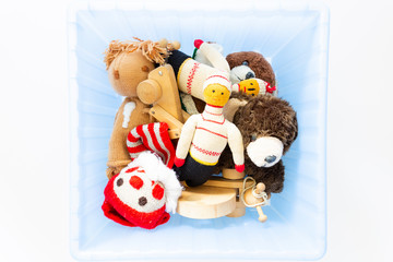 Top view of funny vintage children toys in a blue plastic box on white background. Assortment consists of a clown, a squirrel, a teddy bear, dolls, a wooden grasshopper and a ball.