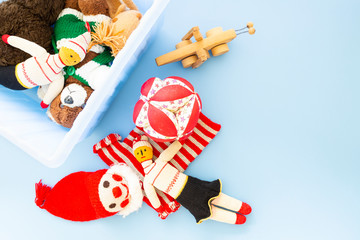 Top view of funny vintage children toys in a blue plastic box on blue background. Assortment consists of a clown, a squirrel, a teddy bear, dolls, a wooden grasshopper and a ball.