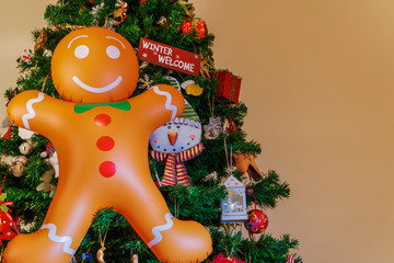 Large inflatable gingerbread man with copy space on a Christmas tree. Air blown seasonal figure hanging before an artificial Christmas tree with festive colorful decorations.