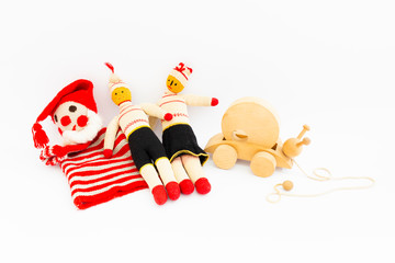Front view of funny vintage children toys on white background. Assortment consists of a clown, a male doll, a female doll, and a wooden snail.
