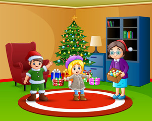Two kids and mother want to decorate a christmas tree