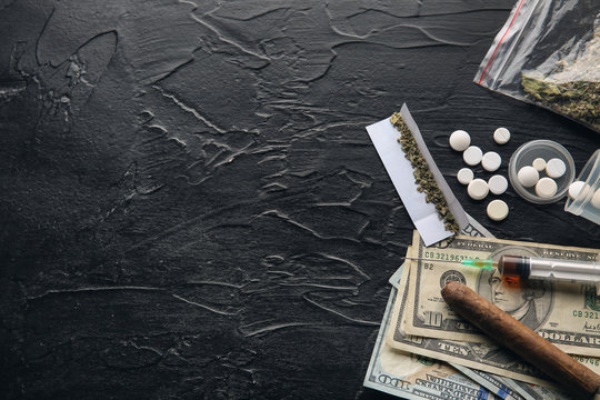 Drugs, cigar and money on dark background. Concept of addiction