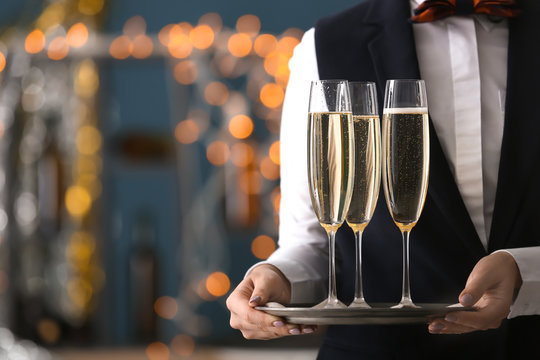 Waitress holding tray with glasses of champagne at party
