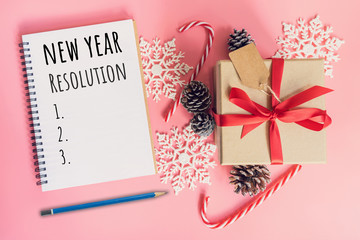 New Year Resolution, top view brown gift box, notebook and christmas decoration for new year on pink pastel color.