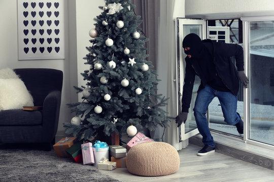 Male thief entering house through window
