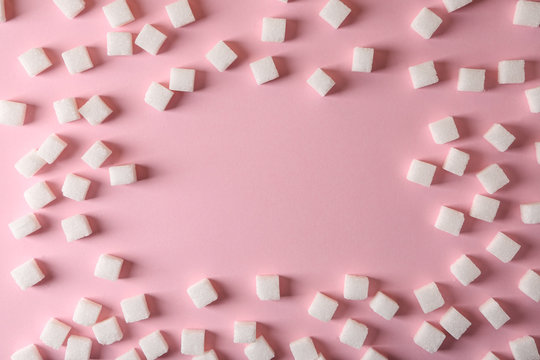Frame made of refined sugar cubes on color background