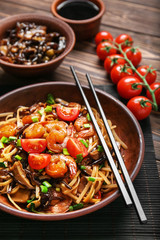 Plate with tasty chinese noodles, mushrooms and vegetables on wooden table, closeup