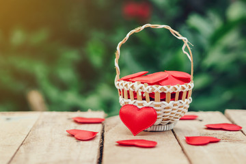 Red heart in basket on wooden table for valentine day and love concept with copy space.
