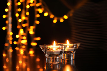 Burning candles against blurred lights