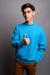 Young handsome Persian teenage boy giving thumb up