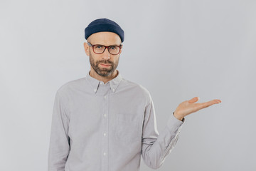 Indoor shot of unshaven Caucasian man holds copy space, demonstrates something against white wall, involved in advertising campaign. Serious male model with bristle stands alone. Isolated shot