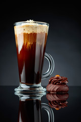 Chocolate dessert with hazelnut and coffee with cream on a black background.