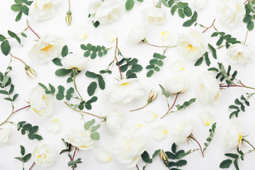 White rose flowers and green leaves on white table from above. Beautiful floral pattern in flat lay styling.