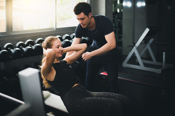 Beautiful woman is exercising and fitness. The trainer gives instructions on how to exercise in the gym.