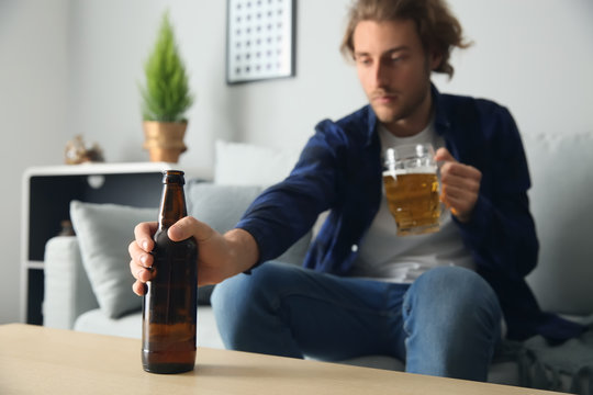 Depressed young man drinking beer at home. Alcoholism concept