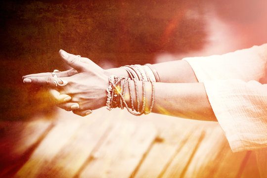 woman hands in yoga symbolic gesture mudra  lot of bracelets and rings   mix with textures