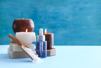 Spa composition with candles and cosmetic products on color background