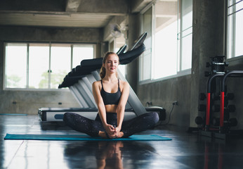 Beautiful athlete put on a sports suit. Stretching a muscle on a yoga mat. Before playing sports in the gym. She is relaxing