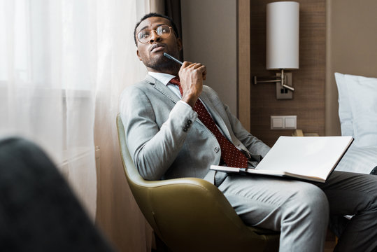 thoughtful african american businessman with diary sitting in hotel room
