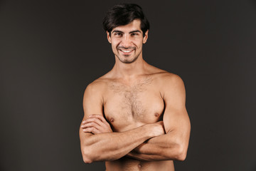 Naked young smiling man posing isolated over dark wall background.