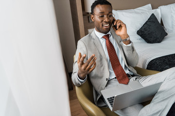 successful handsome african american businessman with laptop talking on smartphone in hotel room
