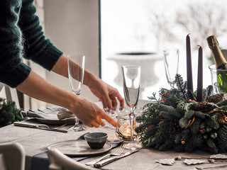 Female hands set the table for Christmas dinner in living room. Snowy winter in window on background. Beautiful served table with decorations, candles, fir branches. Holiday setting