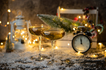 Photo of two champagne glasses on blurred background with Christmas tree, lantern, clock
