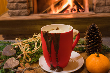 Cozy scene before fireplace with red mug with hot chocolate and christmas decorations.