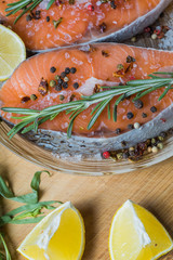 salmon fish on a plate with spices, olive oil and lemon before cooking, flat lay.