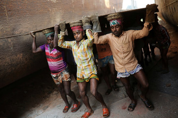 Workers carry a metal sheet at a dockyard in Dhaka