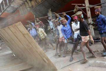Workers throw a metal sheet at a dockyard in Dhaka