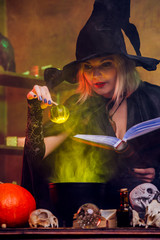 Photo of witch blonde in black hat with book brewing potion in pot with green steam