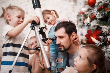 Happy family with telescope on background of decorated New Year's fir
